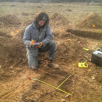 Writing notes over excavated pit.