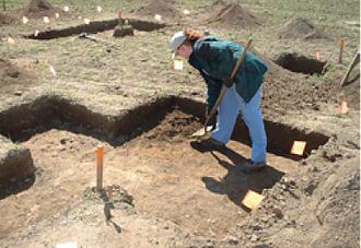 Melanie Hains in partially excavated pit
